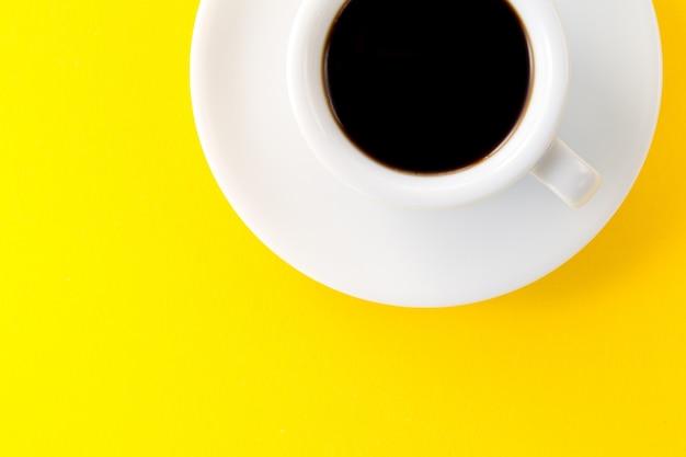Café expresso em pequeno copo de cerâmica branca em fundo amarelo vibrante. mínimo alimento conceito de energia da manhã.
