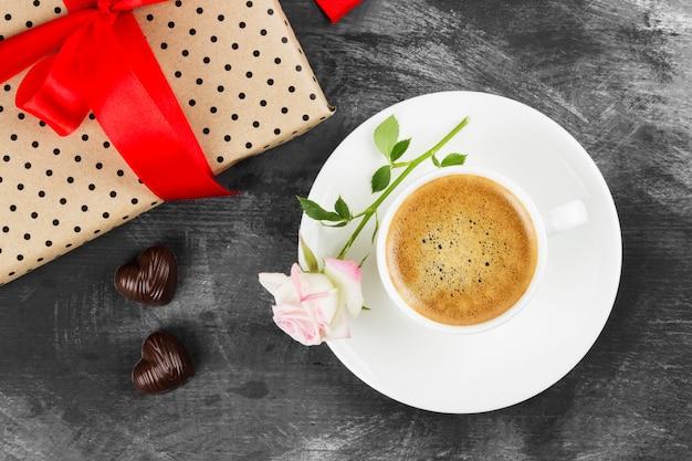 Café expresso em uma xícara branca, uma rosa, um presente com uma fita vermelha e chocolates em um fundo escuro. vista do topo. fundo de alimentos.