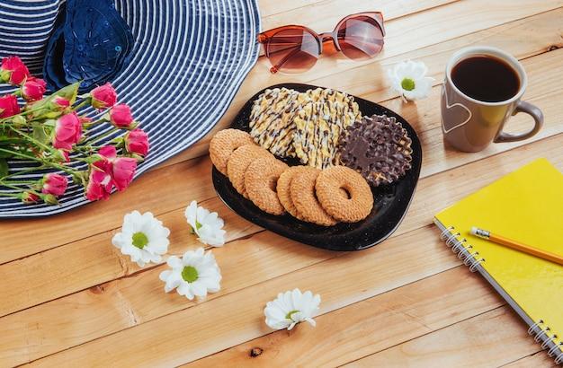 Café expresso fica em uma mesa de madeira com biscoitos, bloco e lápis.