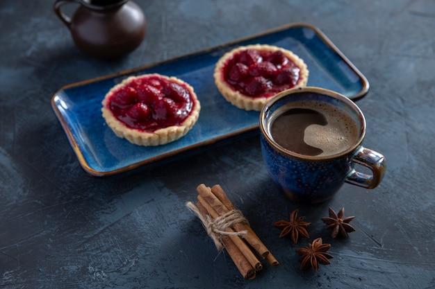 Café expresso framboesa bolos canela em uma mesa escura.