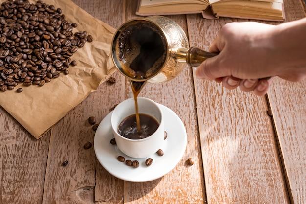 Café expresso fresco em cezve (bule de café turco tradicional) a mão da mulher derrama café em copo branco
