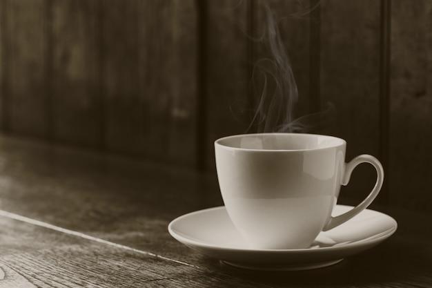 Café expresso ou café preto americano em copo branco na mesa de madeira com espaço de cópia