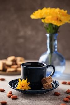 Café expresso preto acabado de fazer em uma xícara azul com um pires e waffles