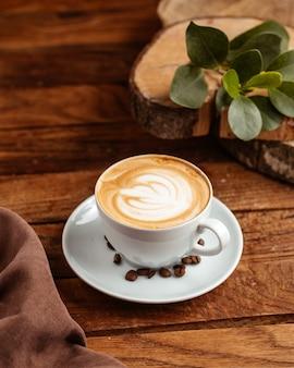 Café expresso quente com sementes de café marrom na mesa de madeira marrom