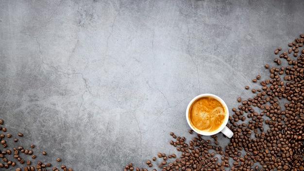 Café expresso quente e grãos de café em piso de cimento velho
