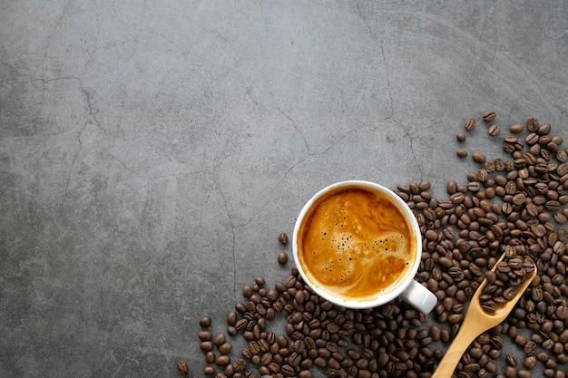 Café expresso quente e grãos de café no antigo fundo do piso de cimento