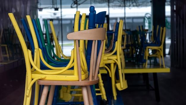 Café fechado com cadeiras elevadas multicoloridas visíveis através da fachada de vidro em bucareste, romênia