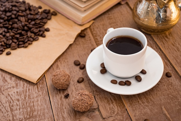 Café fresco abreviado em bebida de manhã cezve (bule de café turco tradicional) em copo branco ao lado de bolas de chocolate