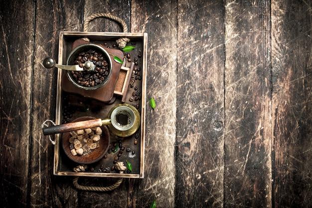 Café fresco com açúcar e grãos de café em uma bandeja velha