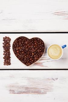 Café fresco com creme. eu amo o conceito de café. pranchas de madeira brancas na superfície.