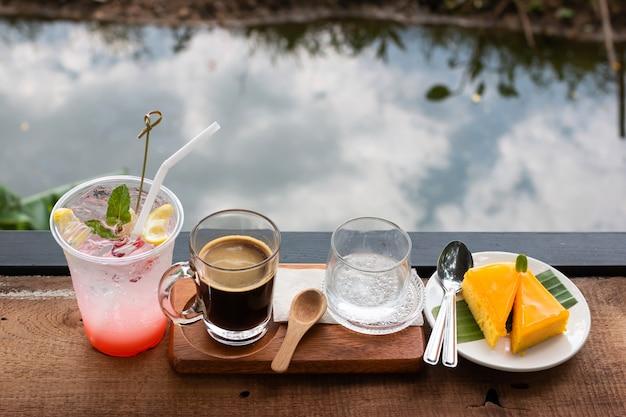 Café fresco em um copo e suco de lichia e bolo de laranja misturado com limão