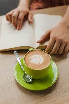 Café fresco latte com latte art perto de pessoa lendo livro na mesa