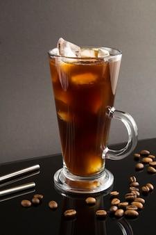 Café fresco no copo de bebida no fundo preto. localização vertical.