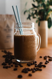 Café frio com canudos azuis rodeados de grãos de café