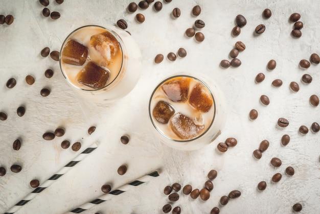 Café frio com caramelo e gelo com cubos de café congelado cappuccino frapuchchino ou café com leite em uma mesa de pedra branca com grãos de café e canudos listrados
