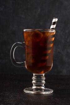 Café frio com gelo e canudo em um copo