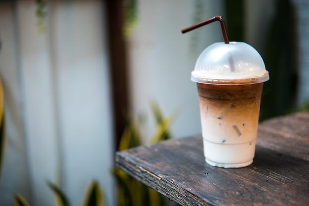Café gelado com canudo na mesa de madeira