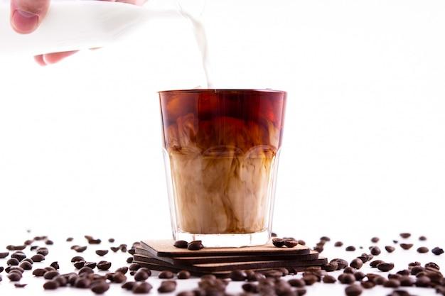 Café gelado com creme derramado na parede branca