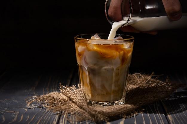 Café gelado com creme derramado na parede escura