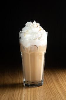 Café gelado com gelo, leite e chantilly em um copo alto transparente sobre uma mesa de madeira