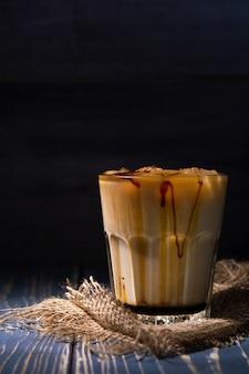 Café gelado com leite na parede escura