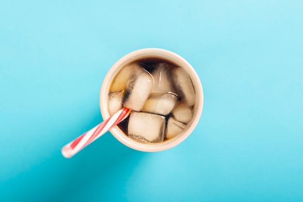 Café gelado de refrescamento em um copo em uma superfície azul. verão de conceito, cola com gelo, cocktail refrescante, sede. vista plana, vista superior