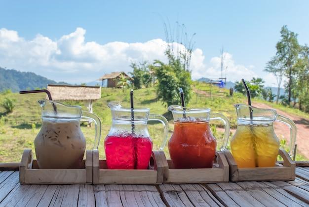 Café gelado e água doce em um frasco de vidro e vista da casa de madeira na montanha.