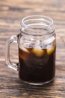 Café gelado e grãos de café no fundo.