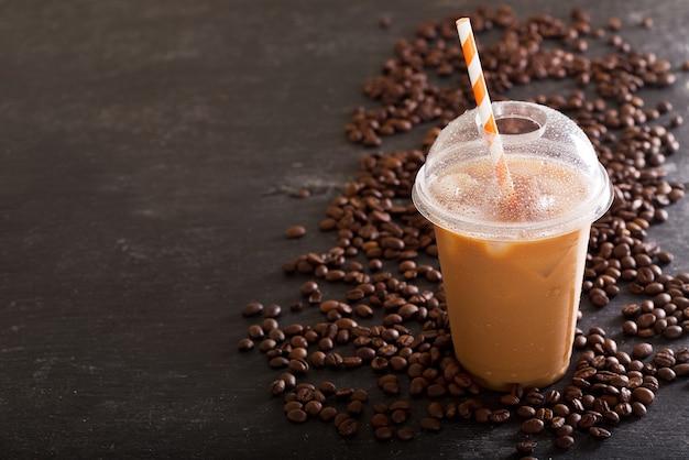 Café gelado em copo de plástico com grãos na mesa escura