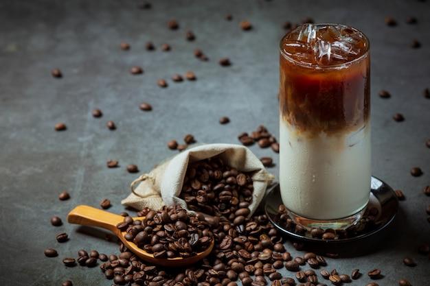 Café gelado em um copo alto com creme coberto com café gelado decorado com grãos de café.