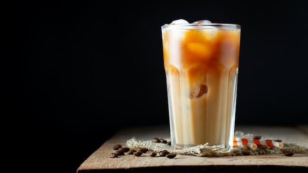 Café gelado em um copo alto com creme derramado.