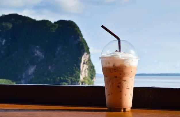 Café gelado em um copo de plástico contra o mar
