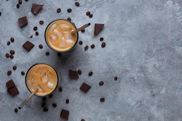 Café gelado em um copo de vidro com um canudo de metal em um espaço cinza de concreto
