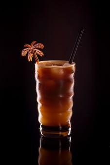 Café gelado em um copo em fundo preto. bebida de café frio ou coquetel com gelo em um fundo escuro