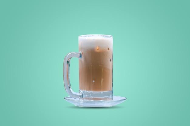 Café gelado em um copo isolado em um fundo de cor verde pastel.