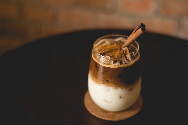 Café gelado em uma mesa de madeira com fundo de parede de tijolosi