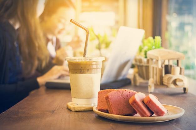 Café gelado no copo de café descartável e bolo de sobremesa durante o tempo de negócios