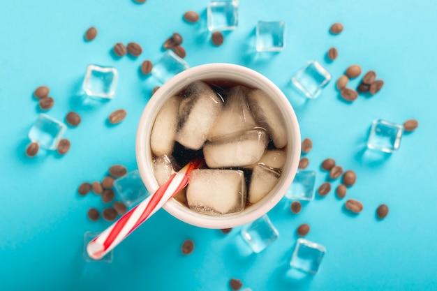 Café gelado refrescante em um copo e cubos de gelo e grãos de café em uma superfície azul. verão de conceito, cola com gelo, cocktail refrescante, sede. vista plana, vista superior