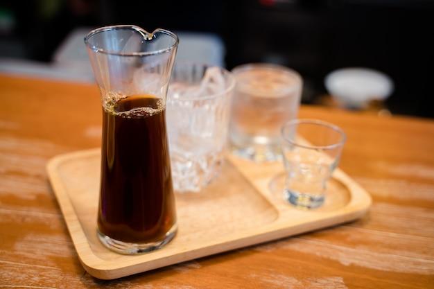 Café gotejado quente servido com um copo de gelo
