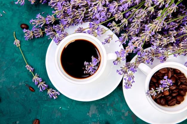 Café, grãos de café em xícaras e flores de lavanda em verde