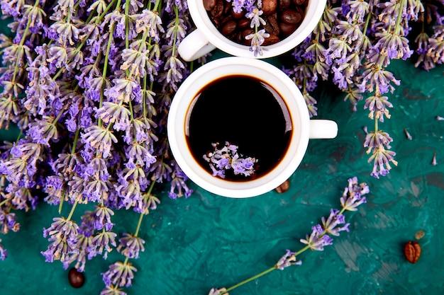 Café, grãos de café em xícaras e flores de lavanda na mesa verde de cima. bom dia conceito. mesa de trabalho de mulher. café da manhã aconchegante. brincar. estilo liso leigo