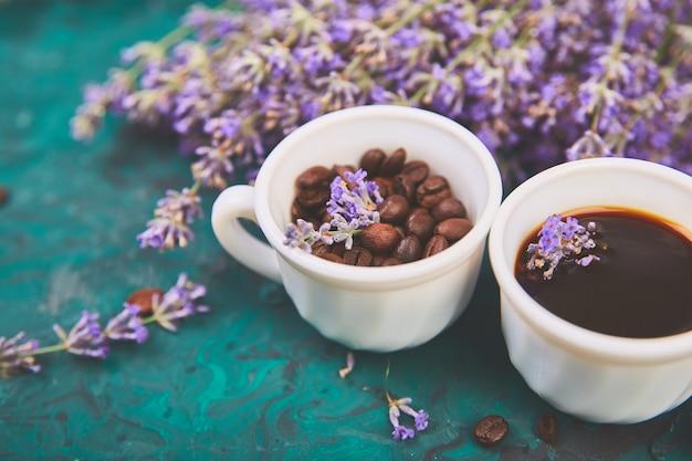 Café, grãos de café em xícaras e flores de lavanda sobre fundo verde
