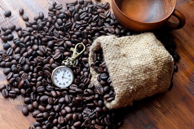 Café, grãos de café pretos, grãos de café pretos marrons e relógios na textura de madeira