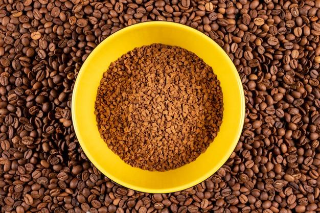 Café instantâneo de vista superior no prato amarelo na superfície de grãos de café