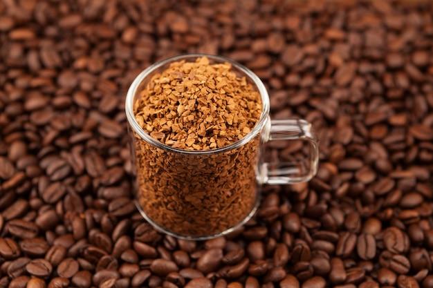 Café instantâneo, liofilizado ou granulado em xícara transparente sobre grãos de café torrados. usado para fazer uma bebida de café dalgon frio.