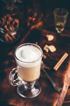 Café irlandês em copo de bebida na superfície de madeira
