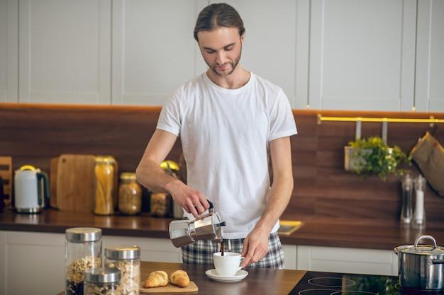 Café. jovem em roupas de casa servindo café na xícara