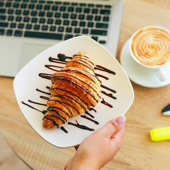 Café, laptop e croissants para mostrar um café da manhã de negócios na mesa do escritório de manhã.