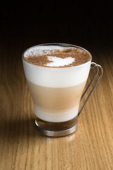 Café latte art com calda, leite e canela em vidro transparente com alça de metal sobre mesa de madeira