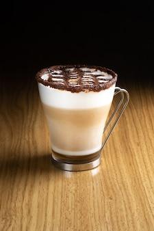 Café latte art com calda, leite e chocolate em vidro transparente com alça de metal sobre mesa de madeira